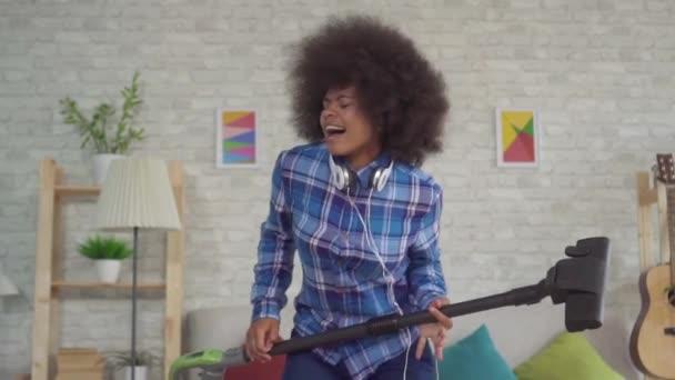 Portré boldog afrikai nő egy afro frizura játszik a mop a porszívó, mint egy gitár lassú Mo