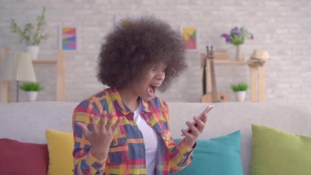 boldog, és meglepett a fiatal afro-amerikai nő afro frizurával néz ki a telefont, és élvezi győztes