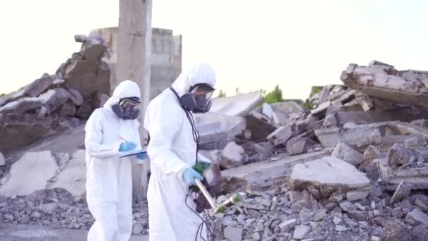 Two scientists in protective suits and masks and a personal ionizing  radiation dosimeter , walk measure radiation on the background of the ruins  of a man-made disaster