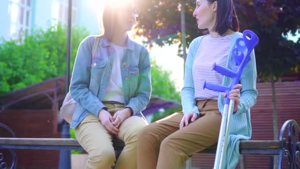 a young woman on crutches sitting on a bench with a friend in the Park,a Sunny day