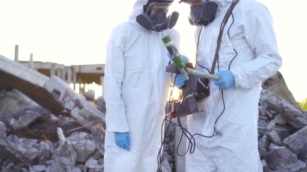 Two scientists in protective suits and masks and make measurements of  personal ionizing radiation dosimeter against the background of the ruins  at sunset