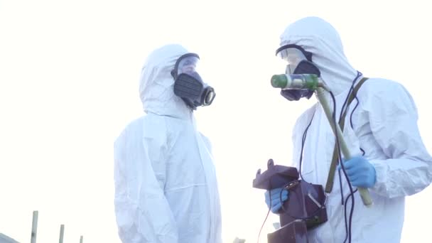 Two scientists in protective suits and masks and make measurements of  radiation against the background of the ruins at sunset