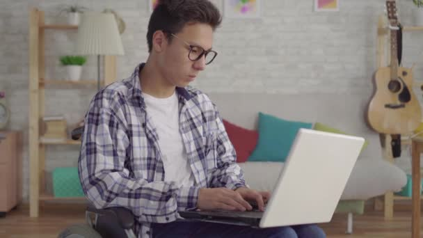 young Asian man in stylish glasses disabled in a wheelchair with a laptop in the living room of the house
