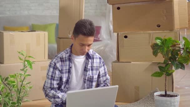 junge nachdenkliche asiatische Mann nach dem Umzug in eine neue Wohnung sitzt an einem Laptop auf dem Boden
