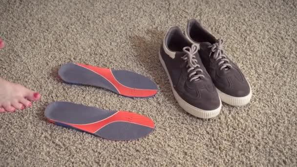 Piedi femminili in piedi sullortopedia vicino alle scarpe da ginnastica