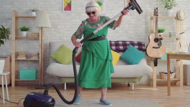 fröhliche, fröhliche Rentnerin mit grauen Haaren und Brille, die einen Staubsauger spielt wie eine Gitarre