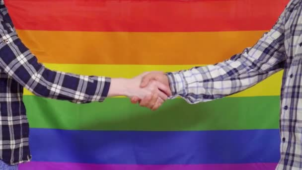 Close up of a handshake on the background of the LGBT flag