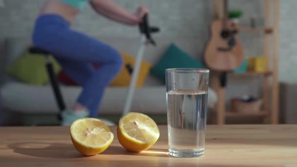 Lemon esik egy pohár vizet, a háttérben a lány részt vesz egy álló kerékpáros lassú Mo