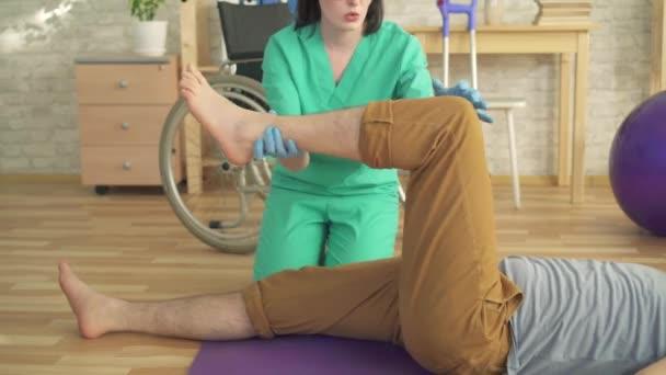 fyzioterapeutka pomáhá člověku, aby se zotavovacích cvičení zavřela