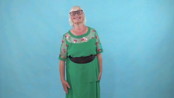 idős nő integetett a kezét köszöntő a kék háttér