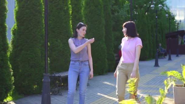 zwei positive junge schöne Frauen, die an einem sonnigen Tag auf der Straße spazieren gehen und sich durch Zeichensprache verständigen