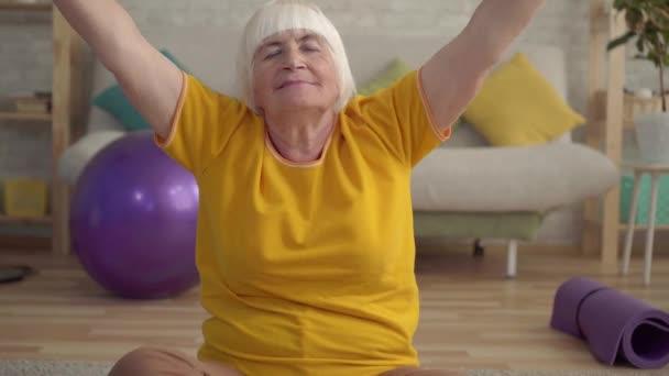 Aktivní pozitivní starší žena dělá jómu na koberci v obývacím pokoji zblízka