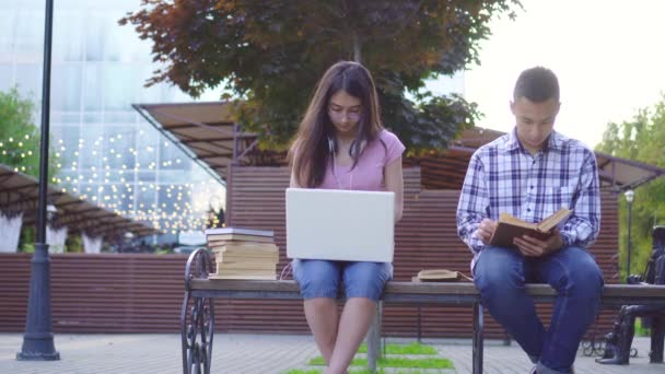 Young asian students man with a book and a woman with a laptop sitting on a bench