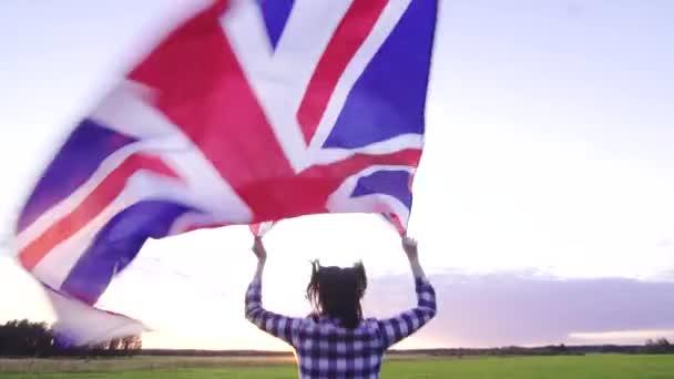 mladá pozitivní žena vede přes pole při západu slunce se zadním výhledem na vlajku UK