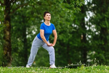 Senior Woman Exercising In Park. Elderly female doing fitness exercises outdoor. Heathy life style concept. Copyspace.