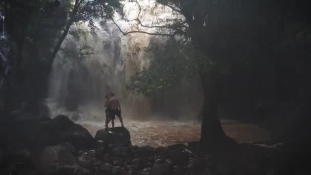 Szerelmes pár alatt egy vízesés egy barlangban. Egy pár szerelmesek. Bali kirándulás. Trópusokon. Utazás. Légi felvétel. Utazási koncepció.
