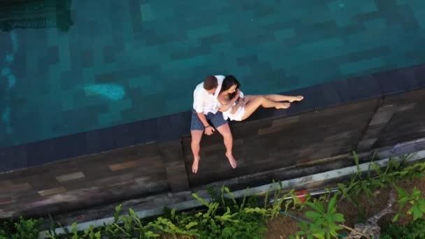 Szerelmes pár a Luxury Resort a romantikus nyári vakáció. Az emberek pihentető együtt Edge úszómedence, élvezi gyönyörű naplemente tengerre néző. Boldog szerelmesek a nászút Travel. Kapcsolat