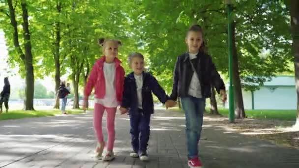 Drei Kinder gehen Hand in Hand im Park. Frontansicht von zwei Mädchen und Jungen, die Spaß haben und den schönen Sommertag im Freien genießen.