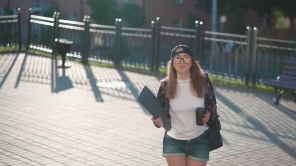 Happy Young female student dressed in casual clothing with cup of coffee and backpack behind her back up the stairs. Woman student holding laptop and drinking coffee. Summer sunset time.