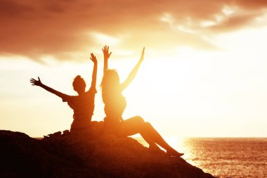 Two happy girls with raised hands against sunset sea