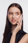 Portréja egy mosolygó nő beszél a Telefonbemenet egy fekete blúz