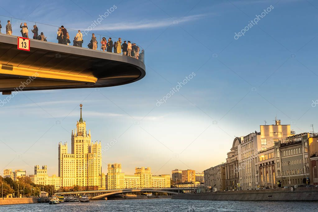 Moscow, Russia-September 20,2018: The view to the Poryachiy bridge over Moskva river at Zaryadye Park in Moscow, the boat on the river and Kotelnicheskaya Stalin s Skyscraper.
