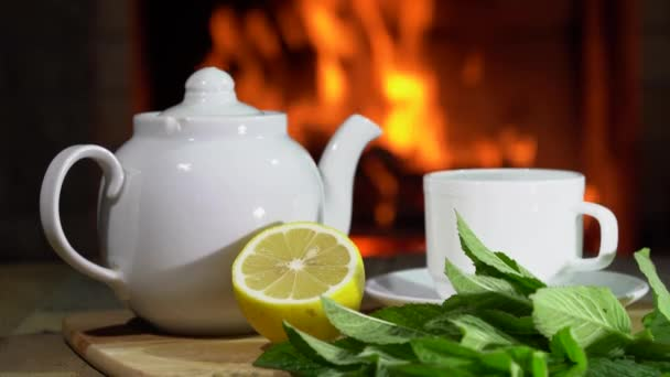 Cozy Fireplace,teapot and cup of Tea with lemon and mint in a country house.