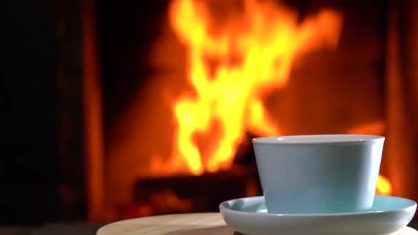 Egy csésze tea forog a kandalló előtt egy vidéki házban..
