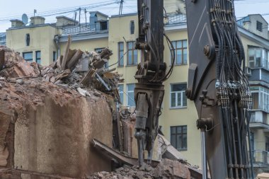 demolition of a multi-storey building with hydraulic shears, for