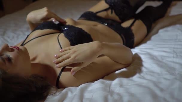Sexy nackte Mädchen in Spitze Dessous liegt auf dem Bett und posiert erotisch aus nächster Nähe. zeitlupe