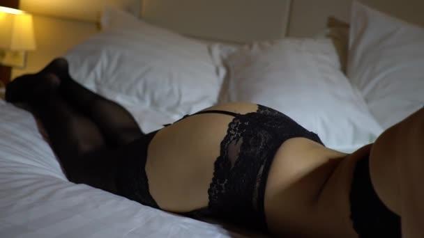 Dívka s krásná štíhlá postava v černém sexy punčochy a prádlo na postele detail