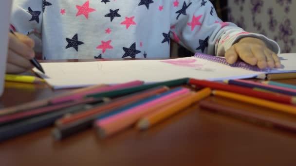Ruce dítěte, které kreslí legrační kresby pastelkami. Dětské fantazie