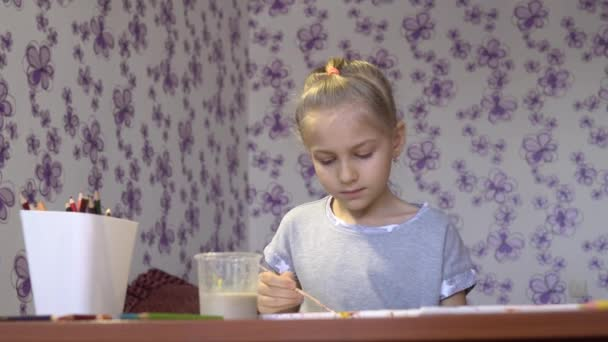 Malá roztomilá holčička kreslí barevné nátěry na list papíru ve svém pokoji