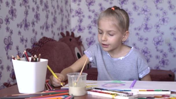 A bájos kislány felhívja az album színes ceruza és festék. Gyermek kreativitás