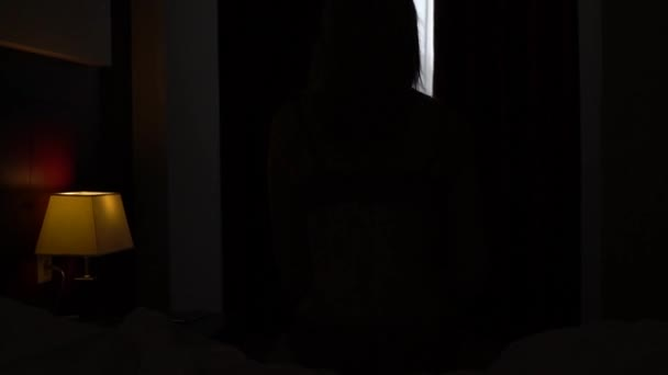 Krásná dívka otevírá záclony na okně. Zpomalený pohyb