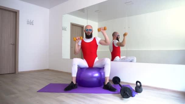4k lustiger Mann mit lustigem Aussehen macht Übungen mit Hanteln, sitzt auf einem Fitnessball in der Halle mit großen Spiegeln