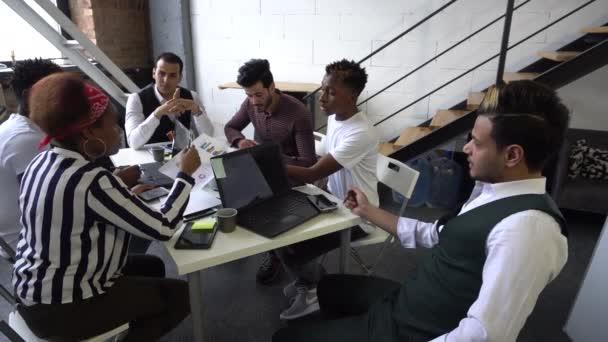 eine Gruppe von Menschen unterschiedlicher Nationalitäten diskutiert ein Investitionsprojekt in einem modernen Büro