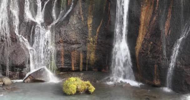 Vodopád teče dolů z útesu do modré vody