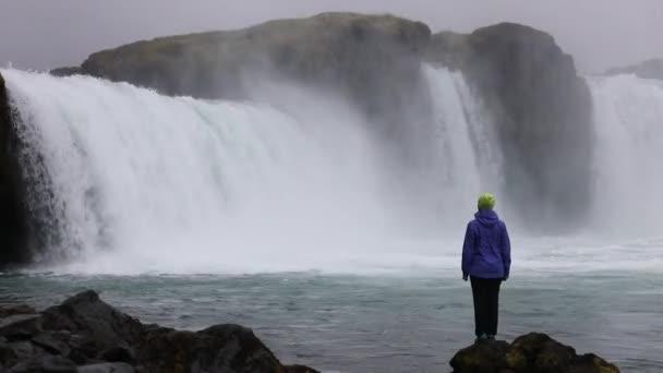 Mladá žena obdivuje silný bouřlivý vodopád, který padá silně podél skalnaté okraje. Křišťálově čistý proud vody, ledovec dopadá na útesu