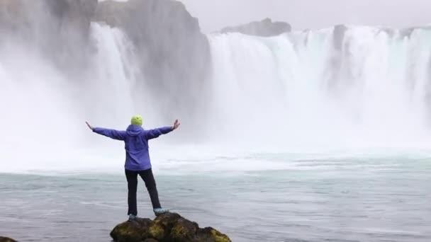 Mladá žena obdivuje silný bouřlivý vodopád, který padá silně podél skalnaté okraje. Křišťálově čistý proud vody, ledovec dopadá na útesu.
