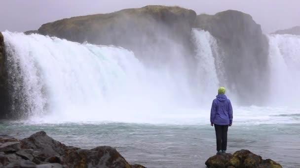 Mladá žena obdivuje silný bouřlivý vodopád, který padá silně podél skalnaté okraje. Na skále spadá křišťálově čistý proud ledové vody. Zpomalený pohyb