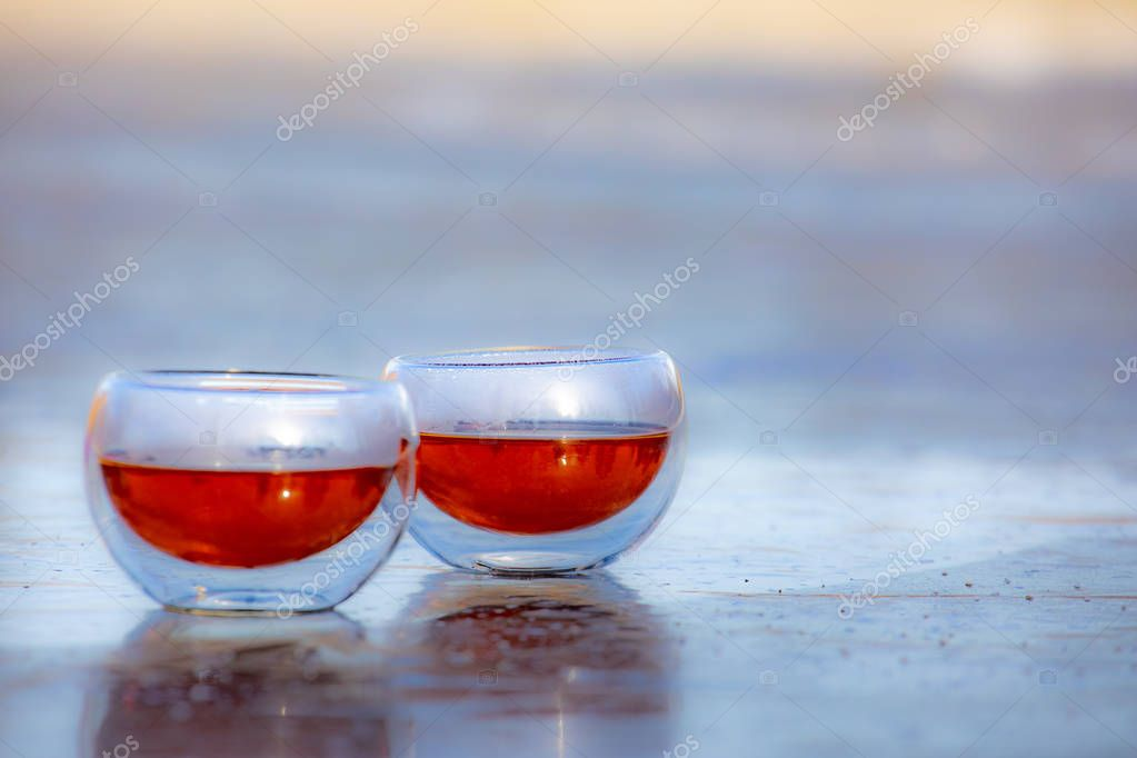 Glass of drink tea coffee wine brandy on the background of nature and ice