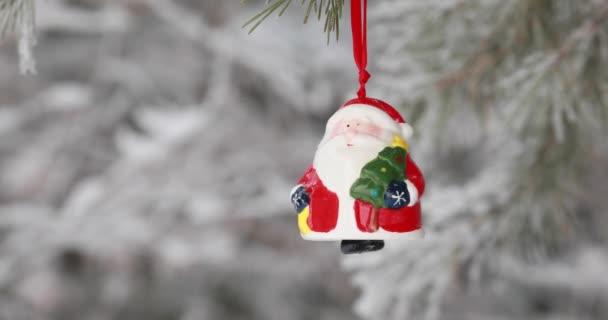 Új év. Karácsonykor és dekorációk. Toy Mikulás lengett egy ág az erdőben. Havazik
