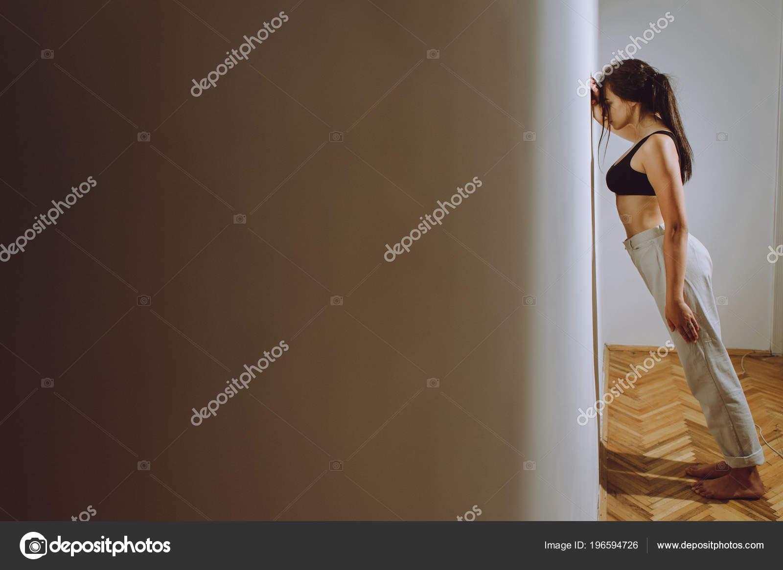 Een mooi meisje leunend tegen muur kamer als een barrière