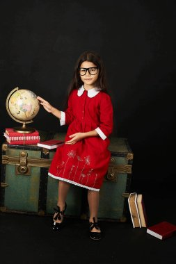 beautiful schoolgirl in red dress looking at globe on black background sitting on a chest