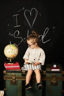 Happy schoolgirl preschool girl with book near school board blackboard sitting on a chest