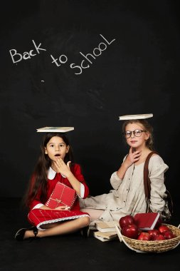two happy beautiful girlfriends schoolgirls have a fun sitting with books on the head and a basket of apples on a black background