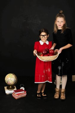two beautiful girlfriends schoolgirls with books and a basket of apples on a black background