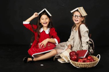 two happy beautiful schoolgirls have a fun sitting with books and a basket of apples on a black background