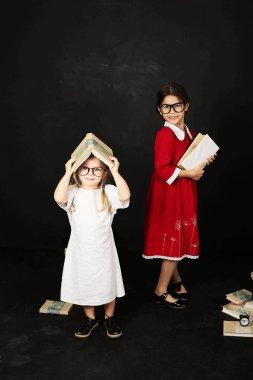two beautiful schoolgirls standing near a blackboard with books on a black background